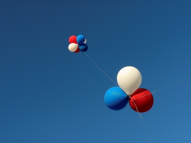 Balloons floating in the air under a blue sky.